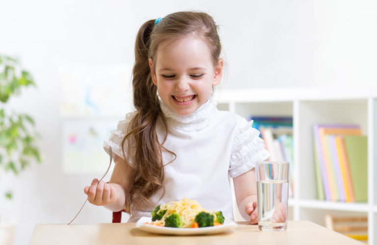 excited 3-6 year old with plate of pasta