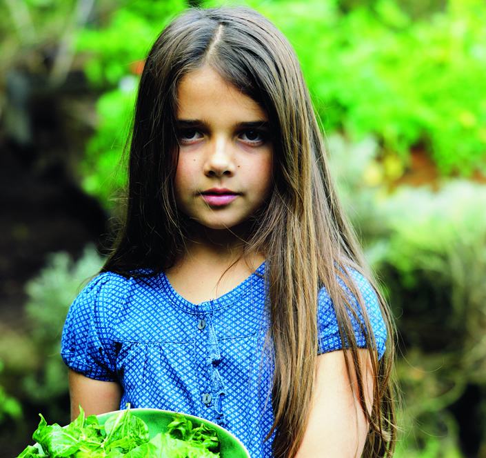 dark haired 3-6 year old carrying lettuce greens
