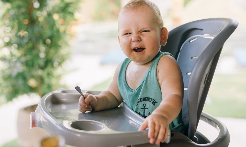 baby in a high chair making a funny face
