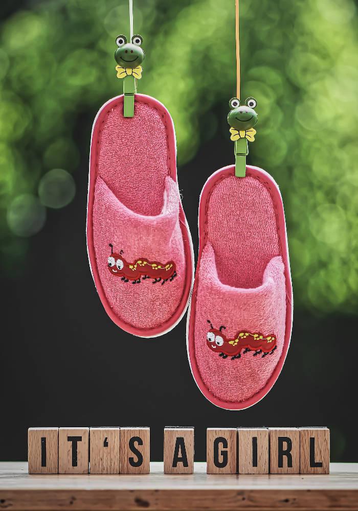 """""""it's a girl"""" wooden blocks below pink slippers"""