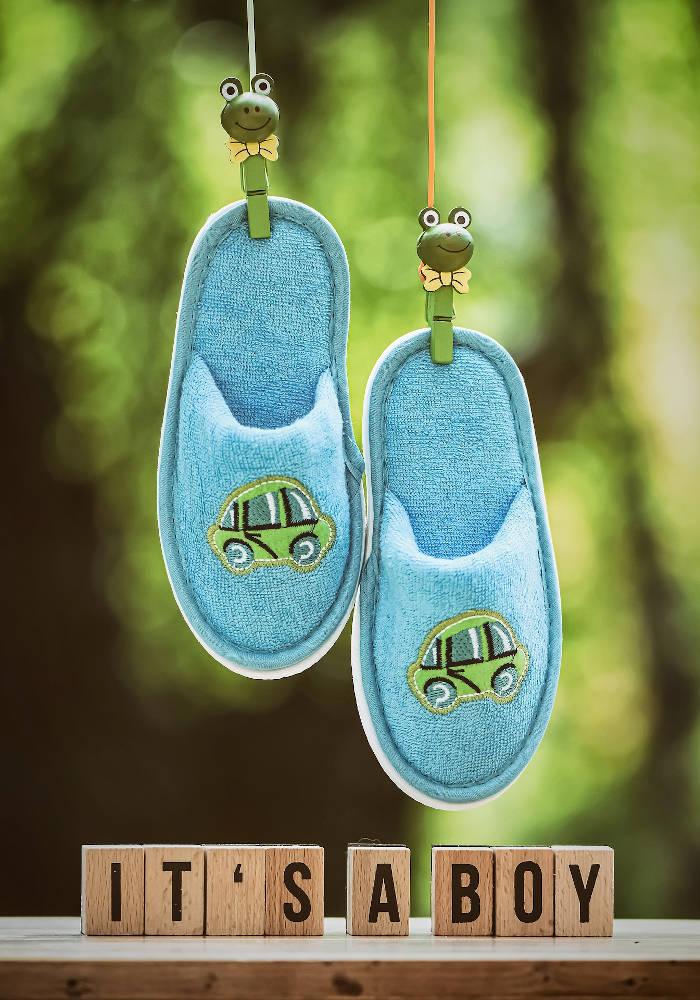 """""""it's a boy"""" wooden blocks below blue slippers"""