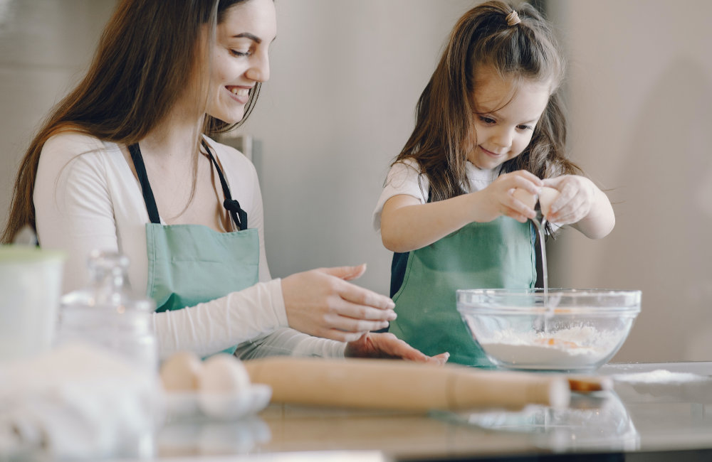 mom and pre-schooler helping break eggs into a bowl