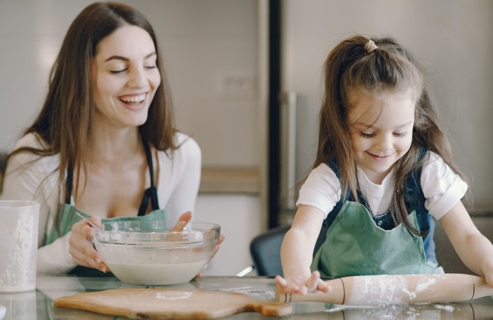 mother and pre-schooler rolling out cookie dough