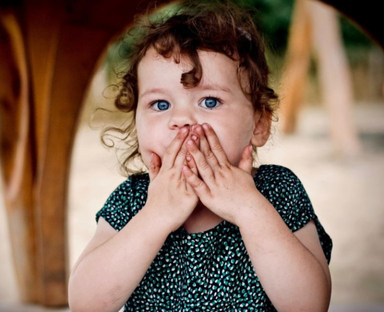 shocked little girl covering her mouth with her hands