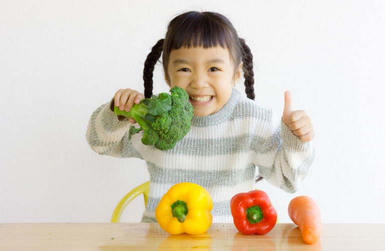 thumbs up from a pre-schooler eating vegetables