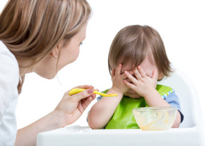 mother trying to feed resistant toddler